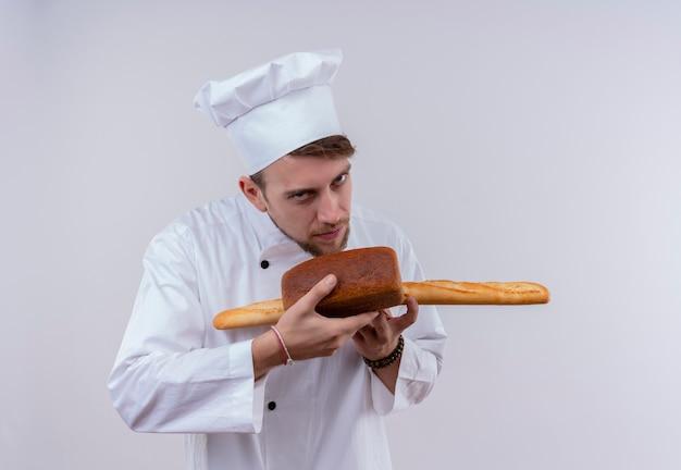 Przystojny młody brodaty szef kuchni w białym mundurze kuchennym i kapeluszu pachnącym chlebem bagietkowym z bochenkiem chleba, patrząc na białą ścianę