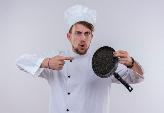Przystojny młody brodaty szef kuchni w białym mundurze kuchennym i kapeluszu wskazującym na patelnię, patrząc z agresywnym wyrazem twarzy na białej ścianie