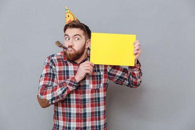 Przystojny młody brodaty urodzinowy mężczyzna trzyma puste miejsce deskę