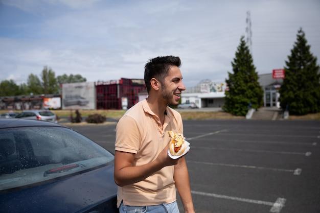 Przystojny młody brunetka mężczyzna je hot dog na parkingu w pobliżu stacji benzynowej.