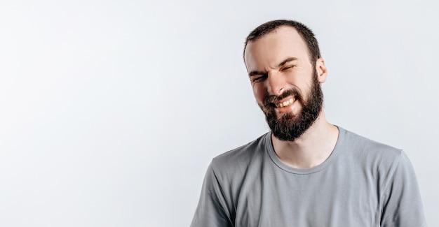 Przystojny młody brunetka mężczyzna marszczący brwi i zamykający oczy, zły na białym tle z miejscem na reklamę makiety