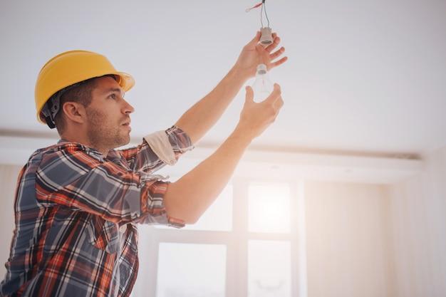 Przystojny młody budowniczy w żółtym budowa hełmie przekręca żarówkę wewnątrz. mężczyzna jest przyglądający up.