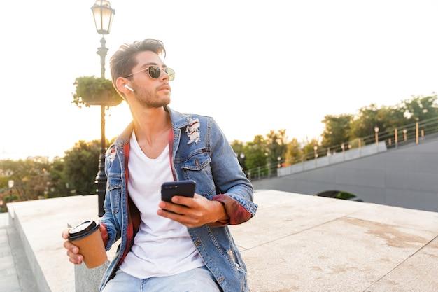 Przystojny młody chłopak chodzenie na zewnątrz przy użyciu telefonu komórkowego, picie kawy i słuchanie muzyki