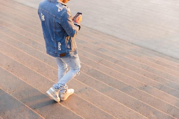 Przystojny młody chłopak chodzenie na zewnątrz za pomocą telefonu komórkowego
