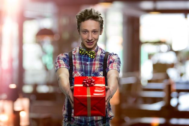 Przystojny młody chłopak daje ci prezent. uczeń w kraciastej koszulce z muszką i czarnymi szelkami. niewyraźne w pomieszczeniu w tle.