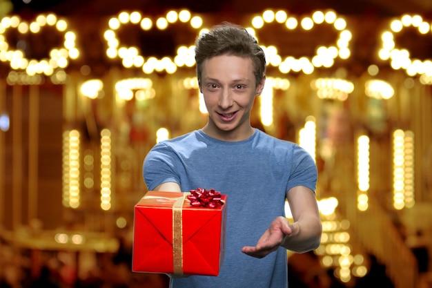 Przystojny młody chłopak daje ci prezent