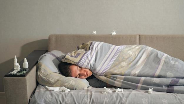Przystojny młody chłopak leżący pod ciepłym kocem w pobliżu zużytych chusteczek na wygodnym łóżku, cierpiący na chorobę w domu