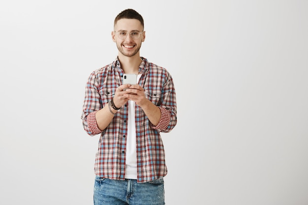 Przystojny młody chłopak pozuje z jego telefonem