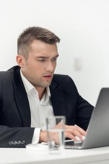 Przystojny, młody chłopak w garniturze pracuje w biurze sprzedaży samochodów. sklep internetowy w laptopie.