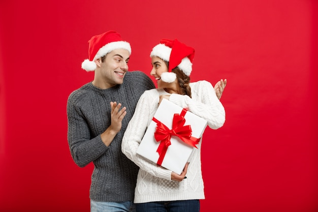 Przystojny młody chłopak w swetrze zaskoczy swoją dziewczynę białym prezentem.
