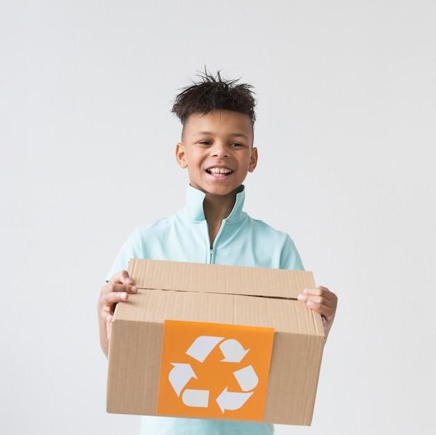 Przystojny młody chłopiec mienie przetwarza pudełko