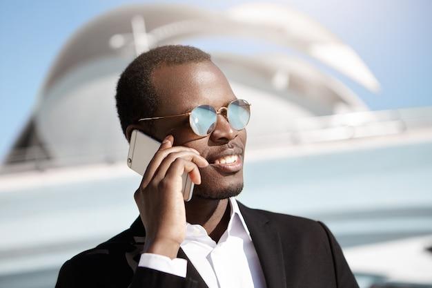 Przystojny młody ciemnoskóry biznesmen w modnych lustrzanych soczewkach i formalnym garniturze trzyma telefon komórkowy, rozmawia ze swoim partnerem, dzieli się wspaniałymi wiadomościami dotyczącymi problemów biznesowych