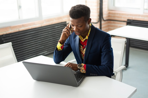 Przystojny młody człowiek afryki przy stole z laptopem w pracy z telefonem