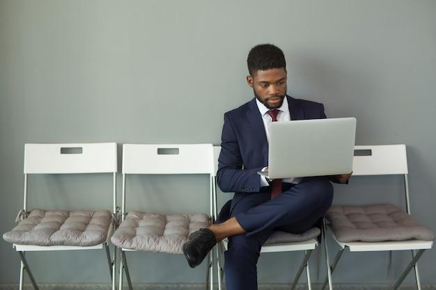 Przystojny młody człowiek afryki w garniturze z laptopem