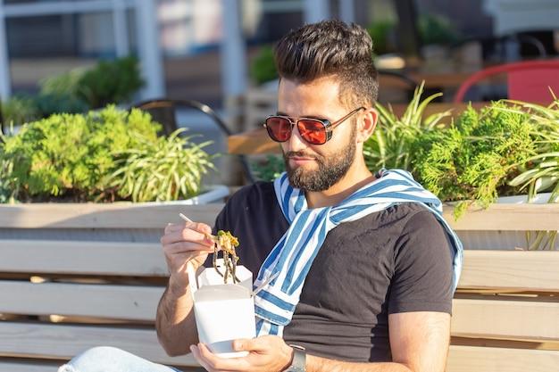 Przystojny młody człowiek arabski trzyma drewniane kije makaron chiński. koncepcja pyszne dania kuchni azjatyckiej.