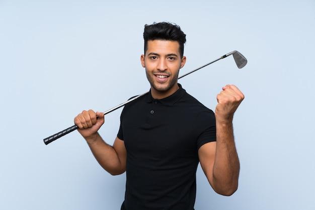 Przystojny młody człowiek bawić się golfa nad odosobnioną błękit ścianą świętuje zwycięstwo