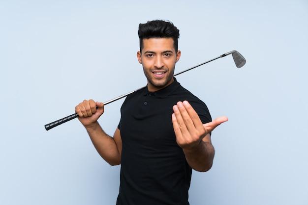 Przystojny młody człowiek bawić się golfa zaprasza przychodzić z ręką. cieszę się, że przyszedłeś