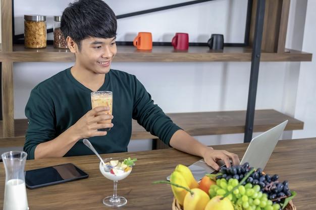 Przystojny młody człowiek chętnie pije herbatę mleczną