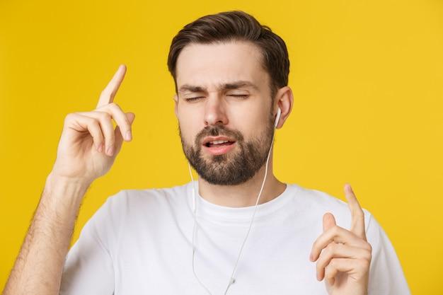 Przystojny młody człowiek cieszy się muzykę nad żółtym tłem.