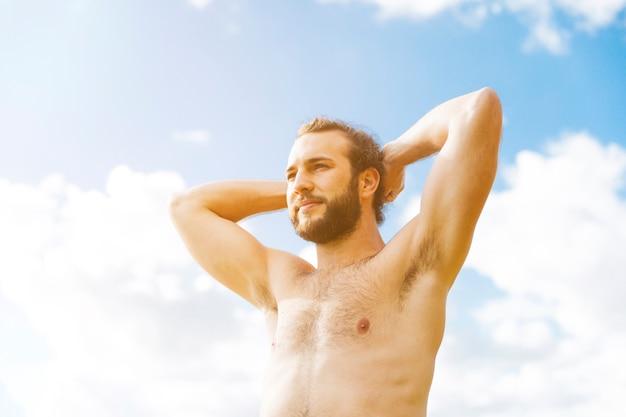 Przystojny młody człowiek cieszy się słońce