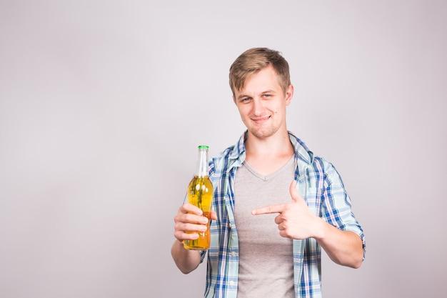 Przystojny młody człowiek czuje się szczęśliwy pokazując kciuk do góry i trzymając butelkę piwa.