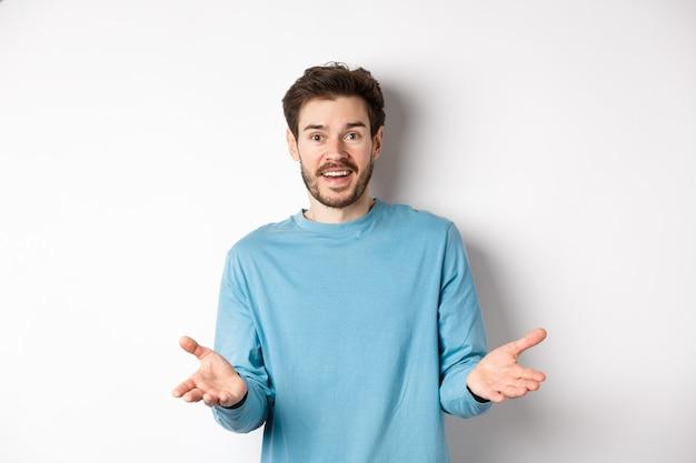 Przystojny młody człowiek czuje się szczęśliwy, wskazując ręce na aparat i chwaląc dobrą robotę, gratulacje gest, stojąc na białym tle.