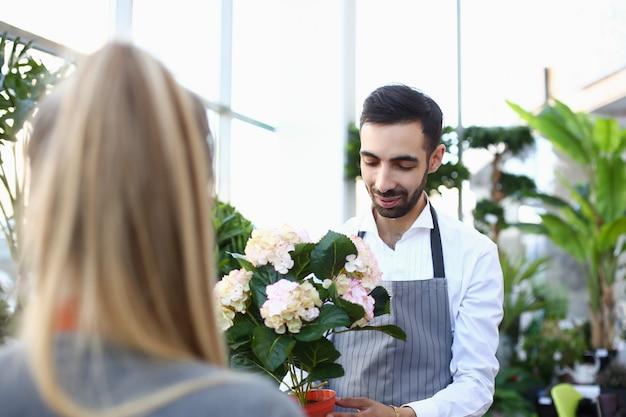 Przystojny młody człowiek daje kwiatowi dama w roślina sklepie