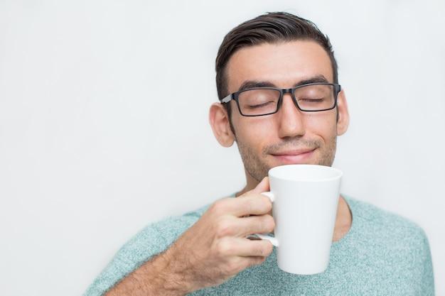 Przystojny młody człowiek enjoying zapachy herbaty