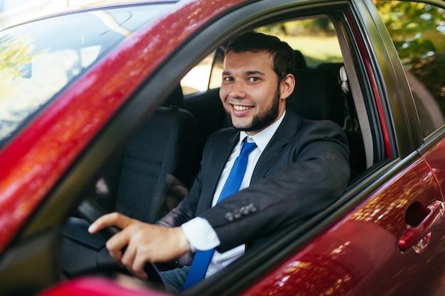 Przystojny młody człowiek jedzie samochód.