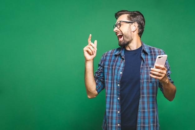 Przystojny młody człowiek jest ubranym hełmofony i trzyma telefon komórkowego podczas gdy stojący przeciw zieleni ścianie i słuchająca muzyka.