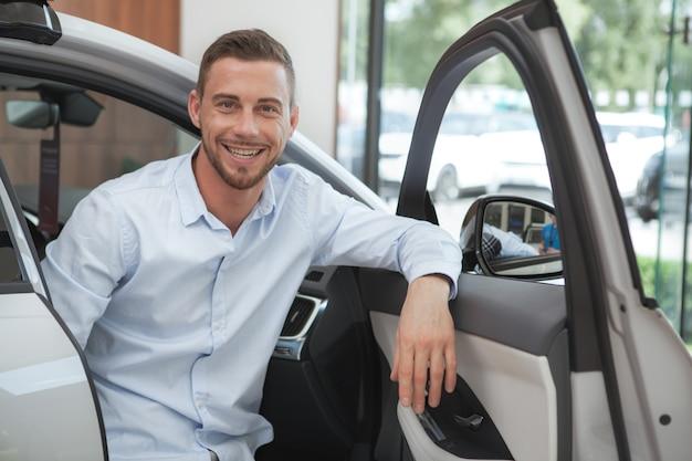 Przystojny młody człowiek kupuje nowy samochód przy przedstawicielstwo handlowe salonem