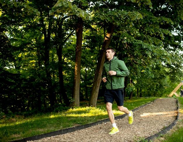 Przystojny młody człowiek lekkoatletycznego działa podczas treningu w słonecznym zielonym parku