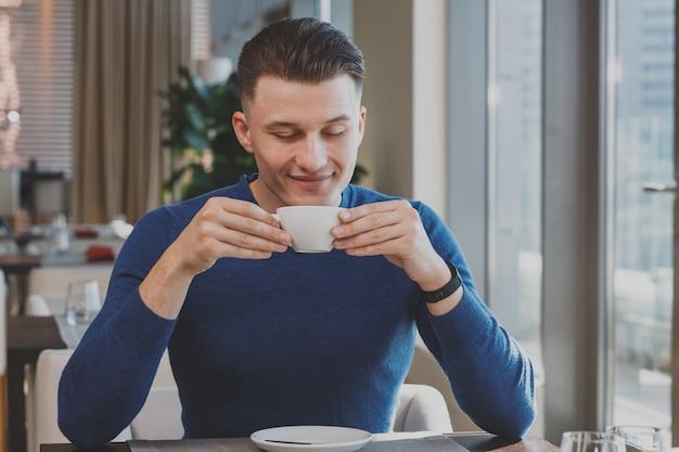 Przystojny młody człowiek ma śniadanie przy kawiarnią