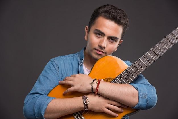 Przystojny młody człowiek mocno ściskając gitarę na ciemnym tle.