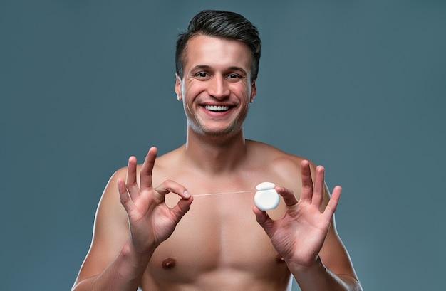 Przystojny młody człowiek na białym tle. portret półnagi muskularny mężczyzna stoi na szarym tle z nić dentystyczną w rękach. koncepcja opieki mężczyzn.