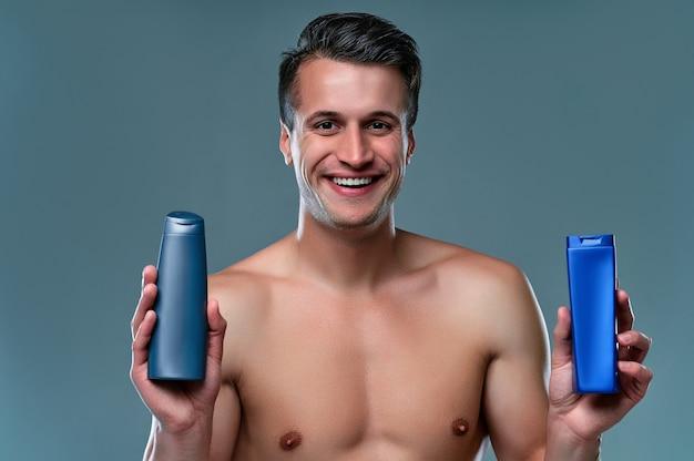 Przystojny młody człowiek na białym tle. portret półnagi muskularny mężczyzna stoi na szarym tle z szamponem w ręce. koncepcja opieki mężczyzn.