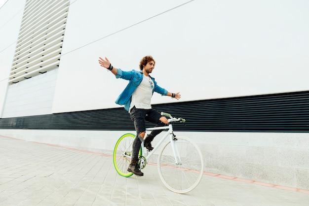 Przystojny młody człowiek na rowerze bez rąk w mieście. koncepcja rowerów