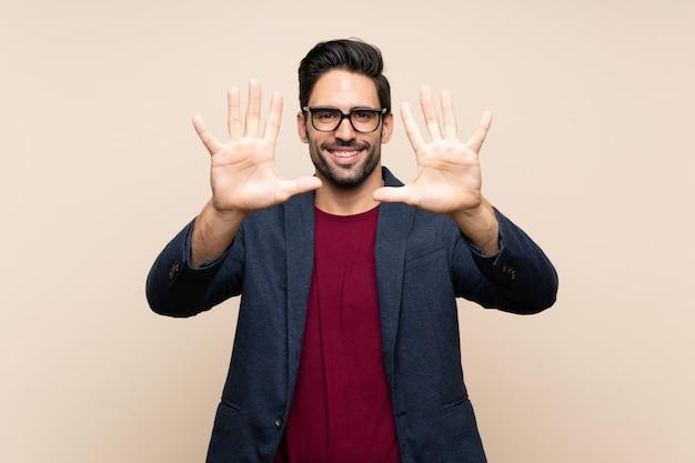Przystojny młody człowiek nad odosobnionym liczeniem dziesięć z palcami