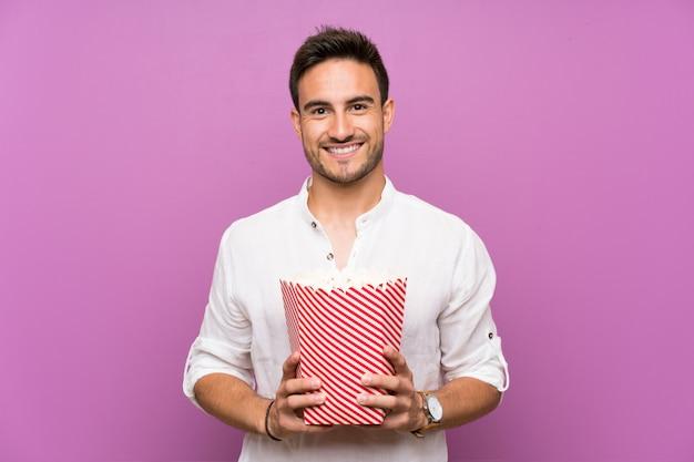 Przystojny młody człowiek nad purpurowymi tła mienia popcorns