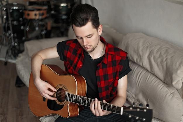 Przystojny młody człowiek nowoczesny gra na gitarze