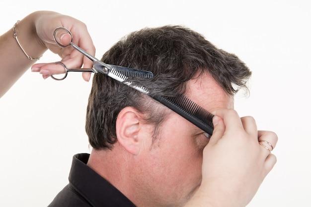 Przystojny młody człowiek o fryzurę wykonane nożyczkami