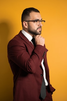 Przystojny młody człowiek okulary w kolorze bordowym patrząc poważnie z ręką złożoną