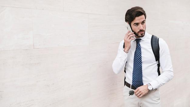 Przystojny młody człowiek opowiada na smartphone