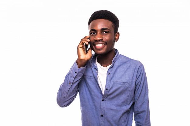 Przystojny młody człowiek opowiada na telefonie na biel ścianie