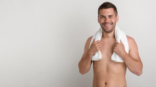 Przystojny młody człowiek patrzeje kamerę przeciw białemu tłu z ręcznikiem na ramionach