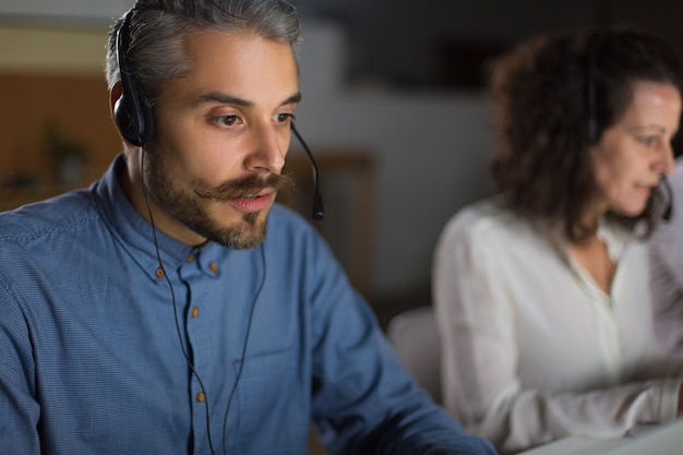 Przystojny młody człowiek patrzeje laptopu ekran z słuchawki