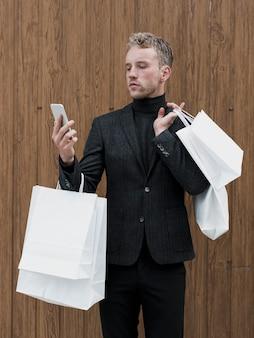 Przystojny młody człowiek patrzeje smartphone