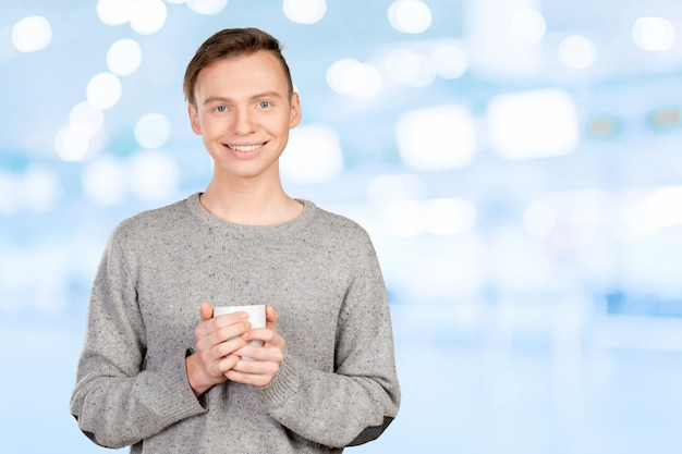 Przystojny młody człowiek pije kawę