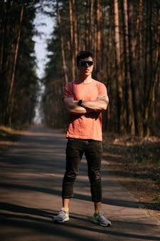 Przystojny młody człowiek plenerowy w parku, chodzi w parku