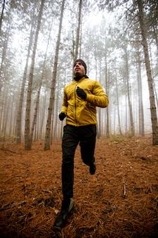 Przystojny, młody człowiek pracuje w lesie jesienią i ćwiczenia na wyścig wytrzymałościowy maraton